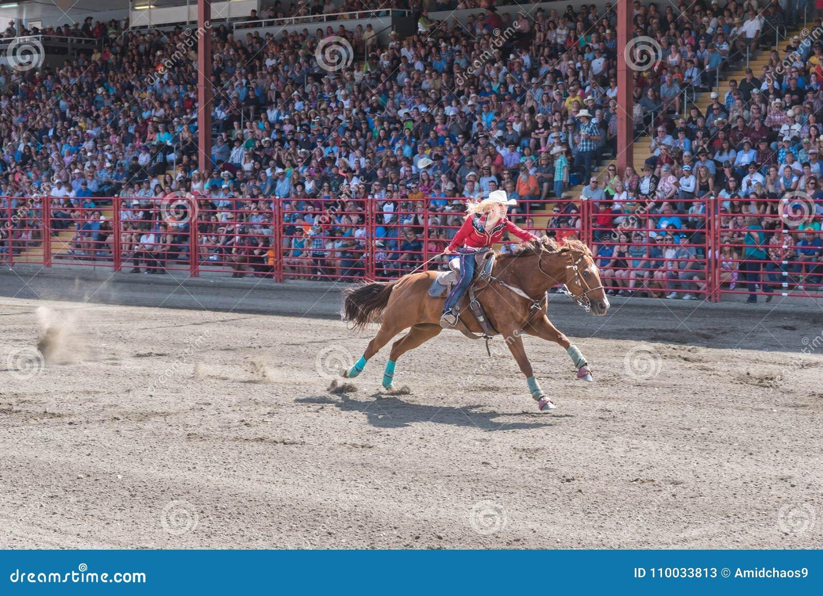 Zdecydowana kobieta pcha konia meta przy lufową bieżną rywalizacją
