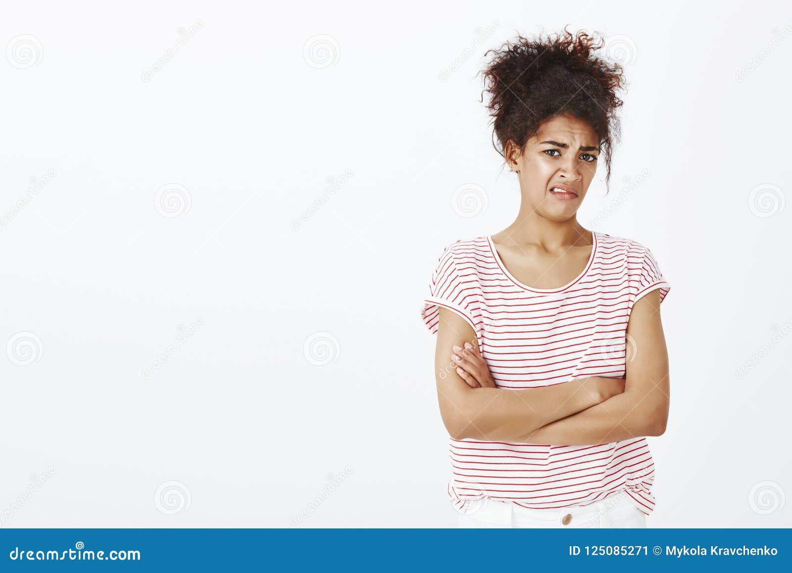 Zdegustowana nieporuszona atrakcyjna kobieta z kędzierzawym włosy w pasiastej koszulce, trzyma ręki krzyżować na klatce piersiowe