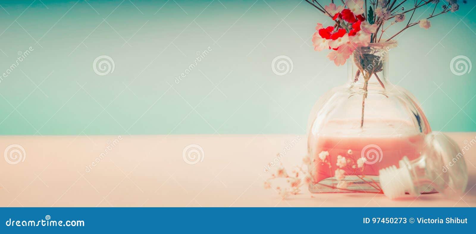Zdrój lub wellness tło z izbową woni butelką, kwiatami na pastelowym tle i, frontowy widok