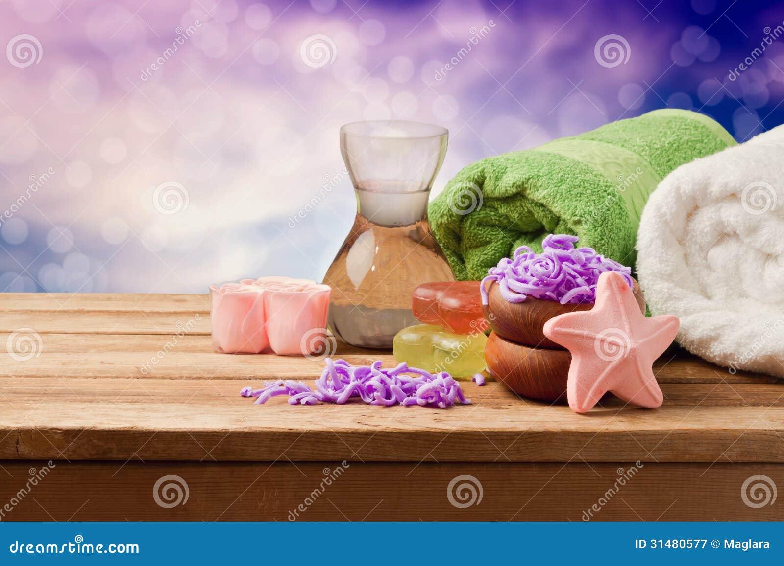 Zdroju położenie z mydłem i ręcznikami na drewnianym stole nad bokeh tłem
