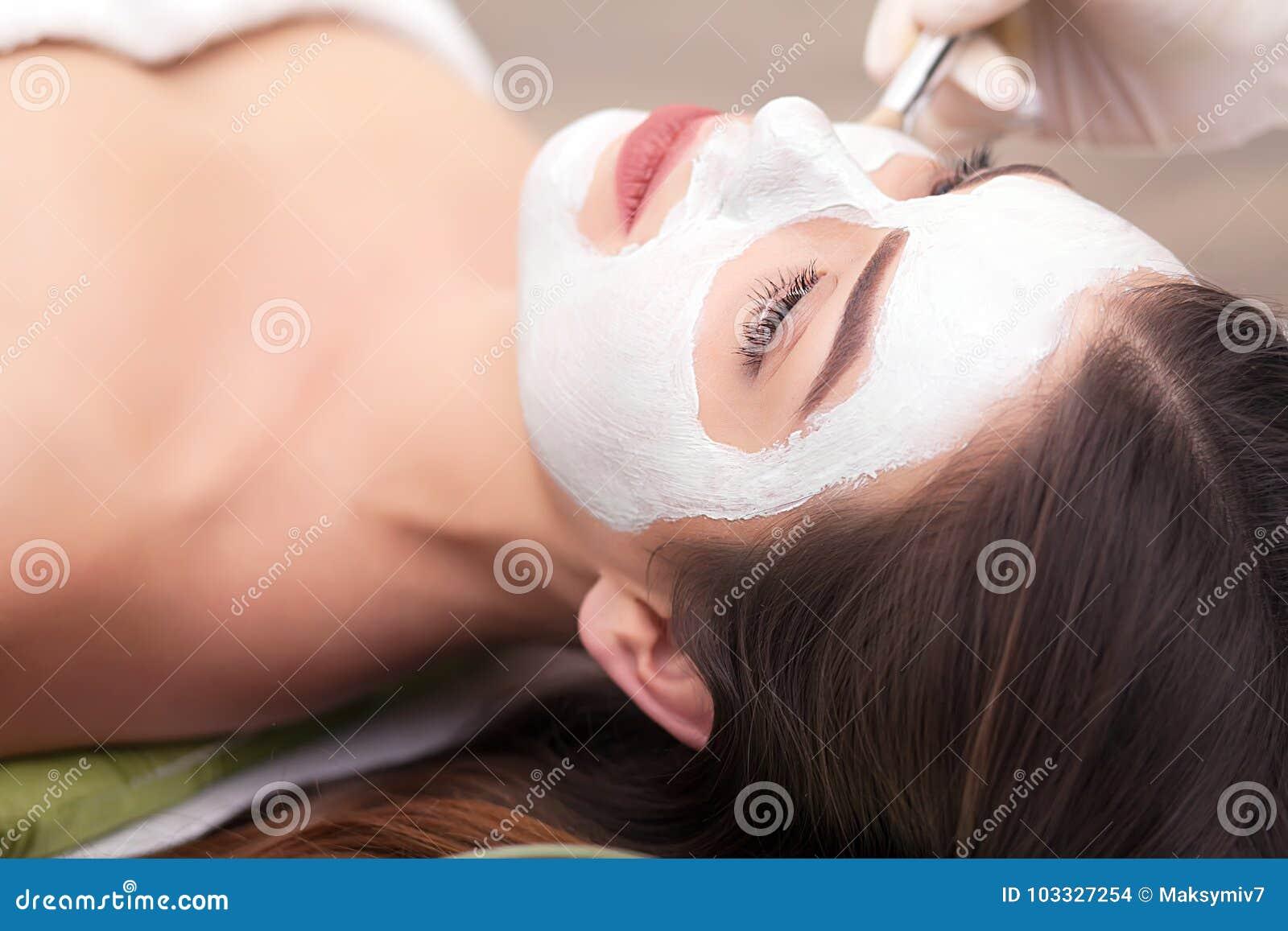 Zdroju pojęcie Młoda kobieta z odżywki twarzową maską w piękno salonie, zamyka up