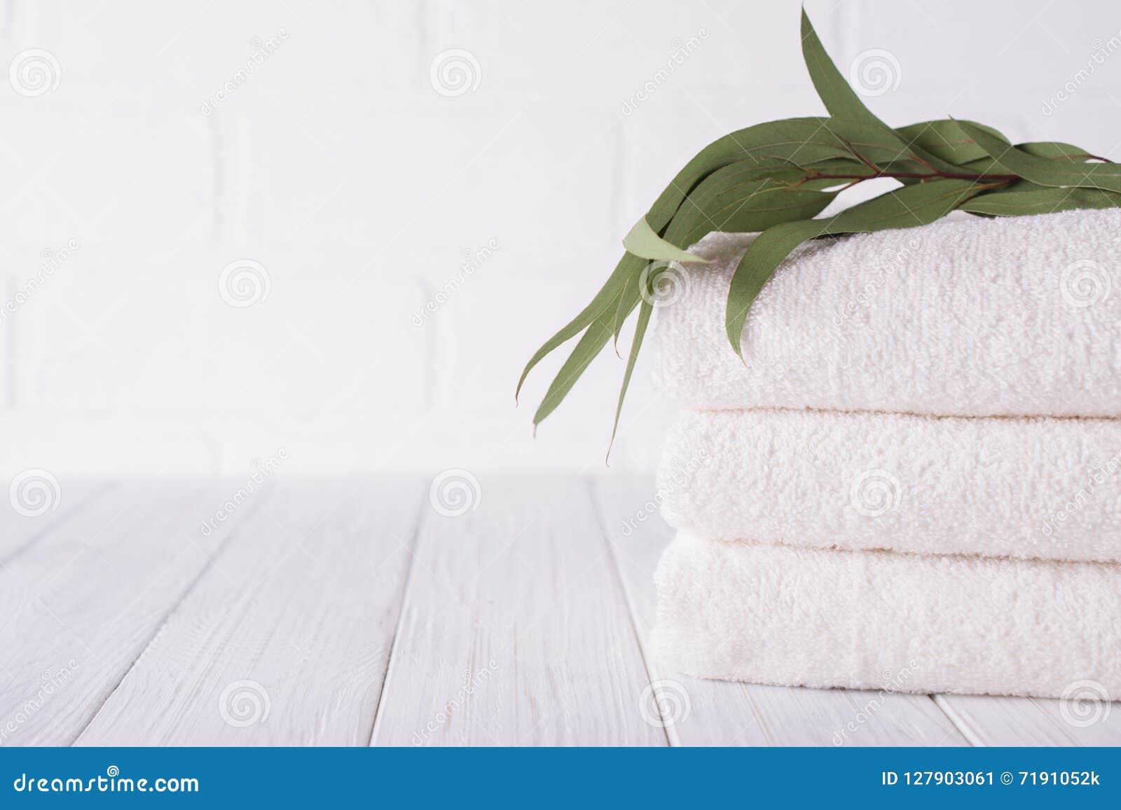 Zdroju skład na drewnianym stole Sterta trzy białego puszystego kąpielowego ręcznika z eukaliptus gałąź
