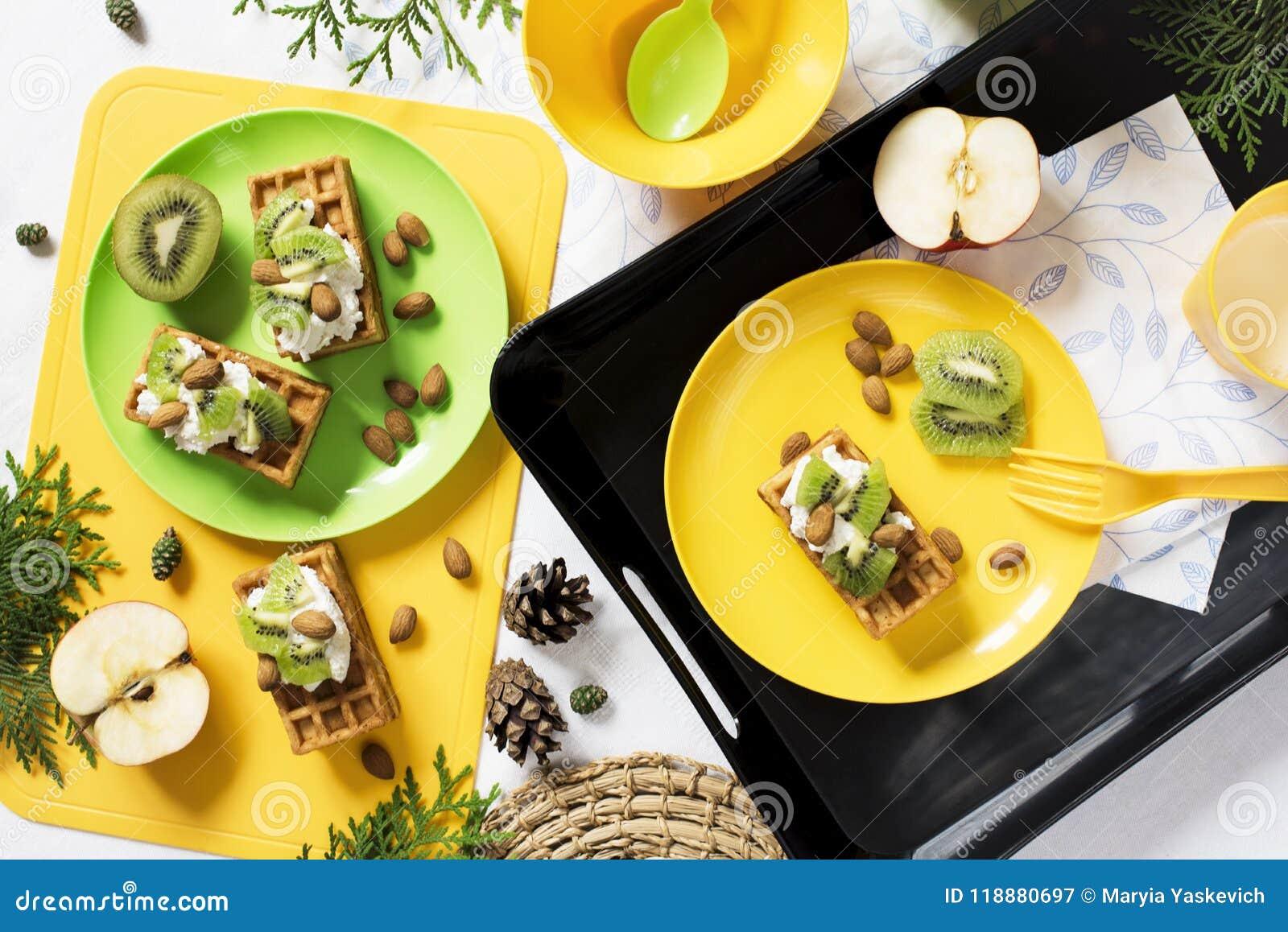 Zdrowa żywność Śniadanie z goframi, kiwi, migdał, miękki ser, jabłko, mleko na białym tle