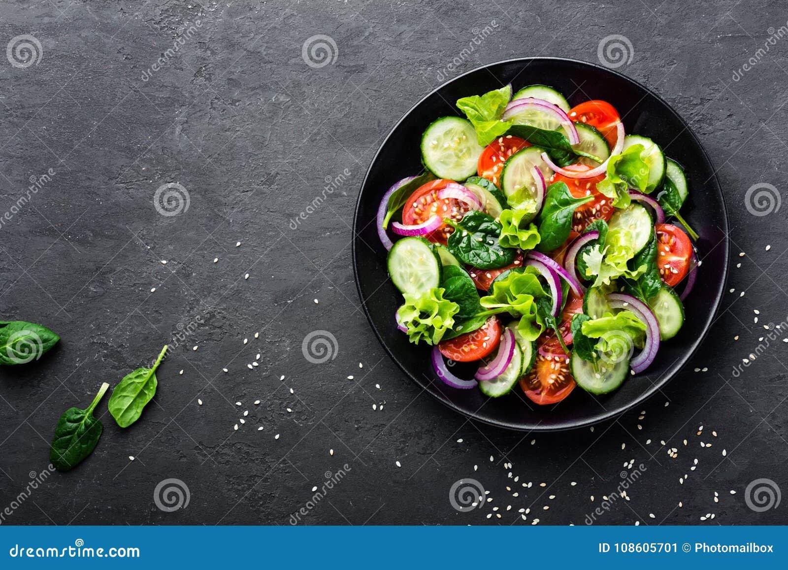 Zdrowa jarzynowa sałatka świeży pomidor, ogórek, cebula, szpinak, sałata i sezam na talerzu, Dieta menu