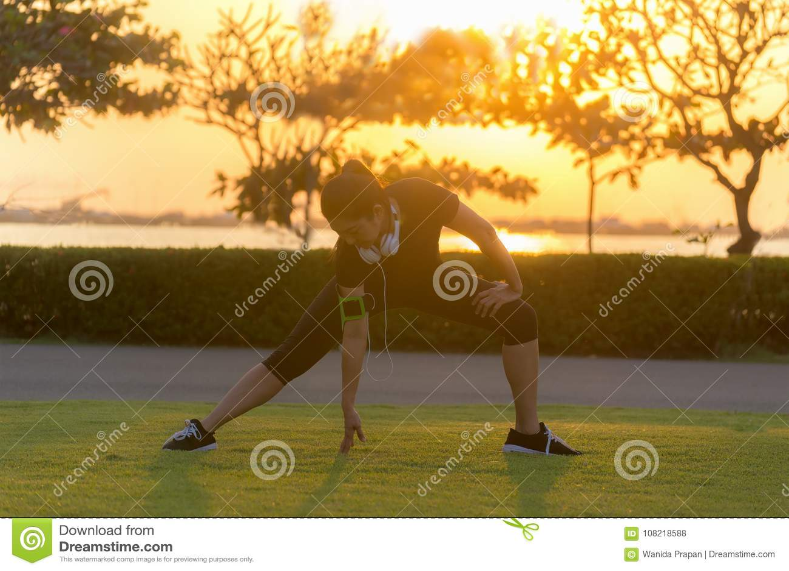 Zdrowego biegacza kobiety atlety azjatykci rozciąganie iść na piechotę dla rozgrzewkowego up przed biegać w parku na zmierzchu