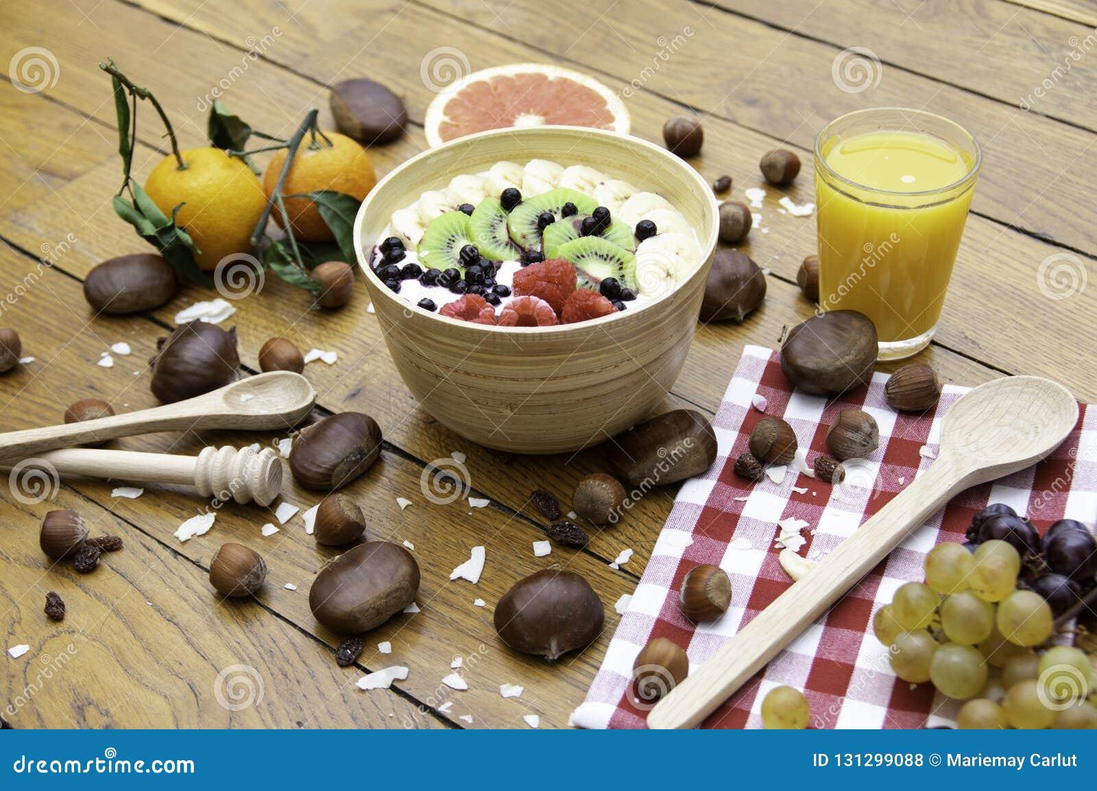 Zdrowy świeży naturalny śniadanie z jogurt owoc dokrętkami na drewno stole i sokiem