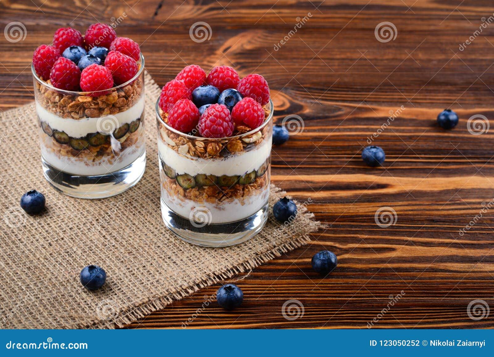 Zdrowy czarnej jagody i malinki parfait w szkle na nieociosanym b