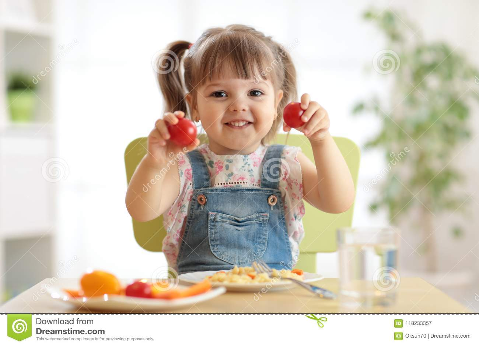 Zdrowy dzieciaka odżywiania pojęcie Rozochocony berbeć dziewczyny obsiadanie przy stołem z talerzem sałatka, warzywa, makaron w p