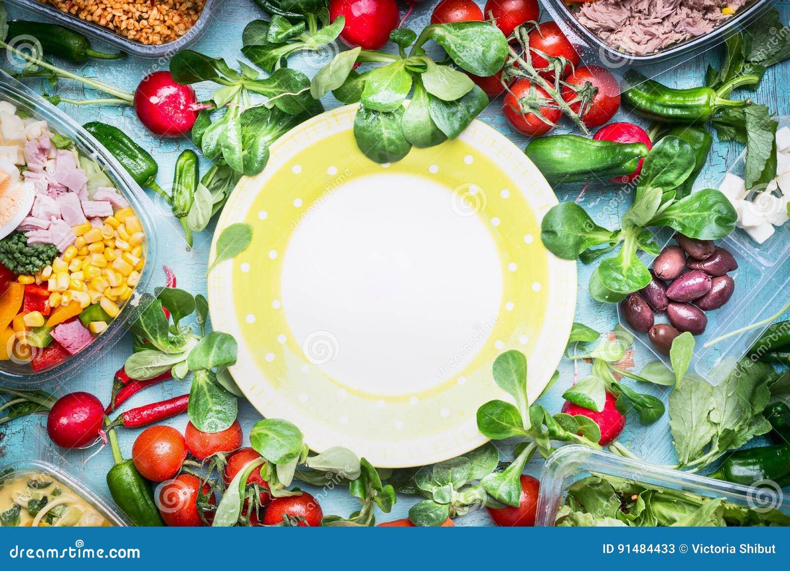 Zdrowy lunchu przygotowanie Różnorodni warzywa i sałatkowi puchary w klingerycie pakuje wokoło pustego talerza