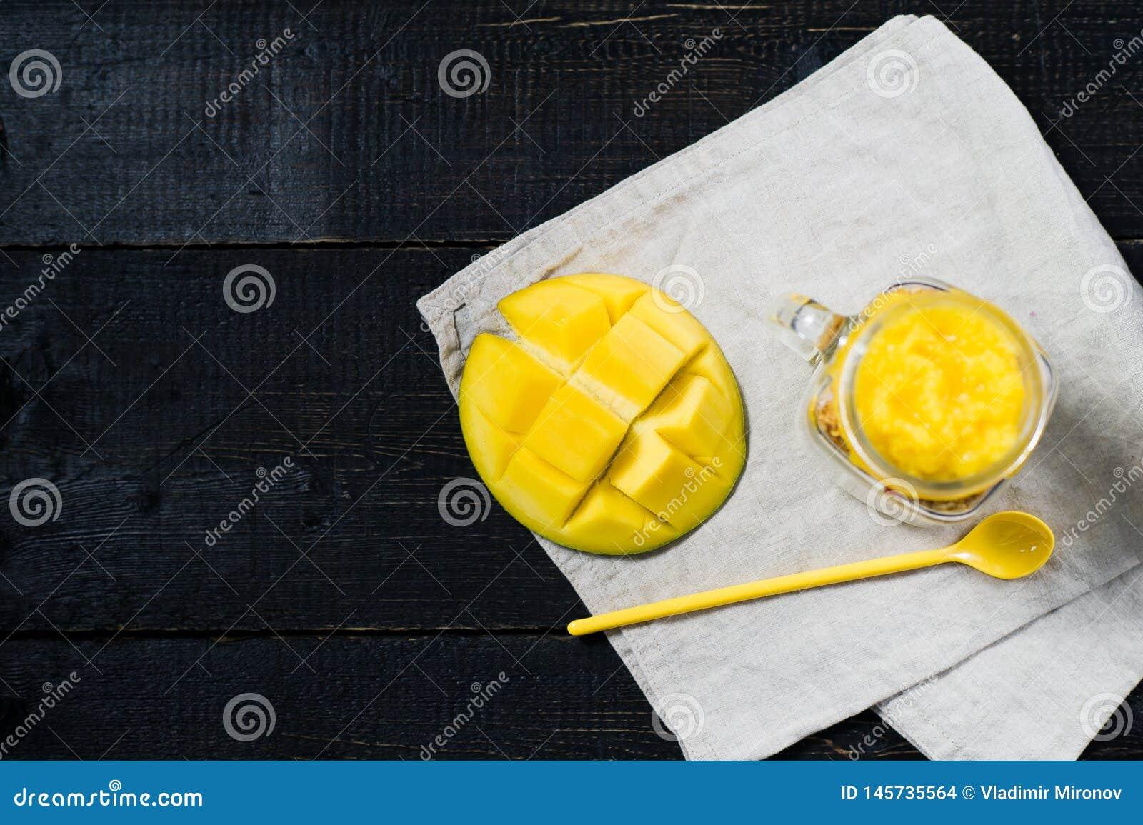 Zdrowy ?niadaniowy muesli i jogurt z mangowym smoothie w szklanych kamieniarz?w s?ojach