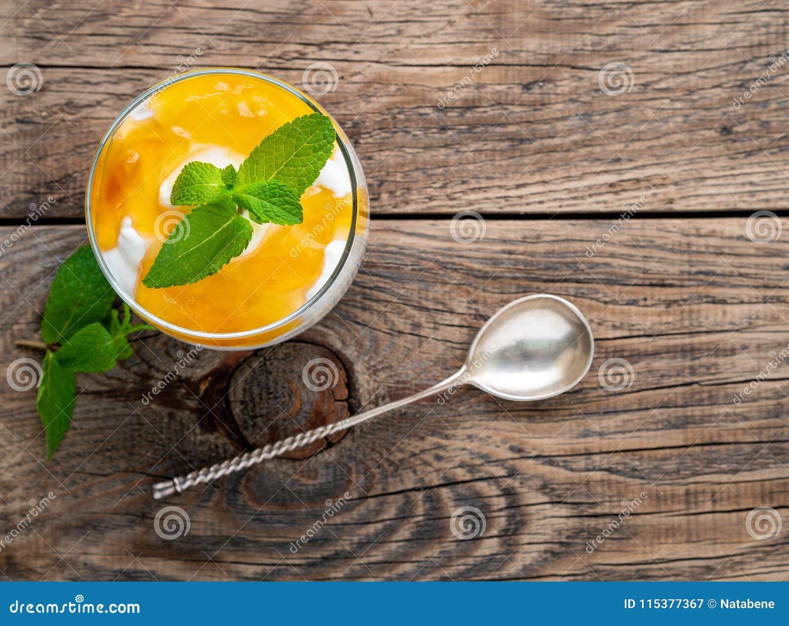 Zdrowy płatowaty deser z jogurtem, banan, mango, krakers na drewnianym tle, odgórny widok