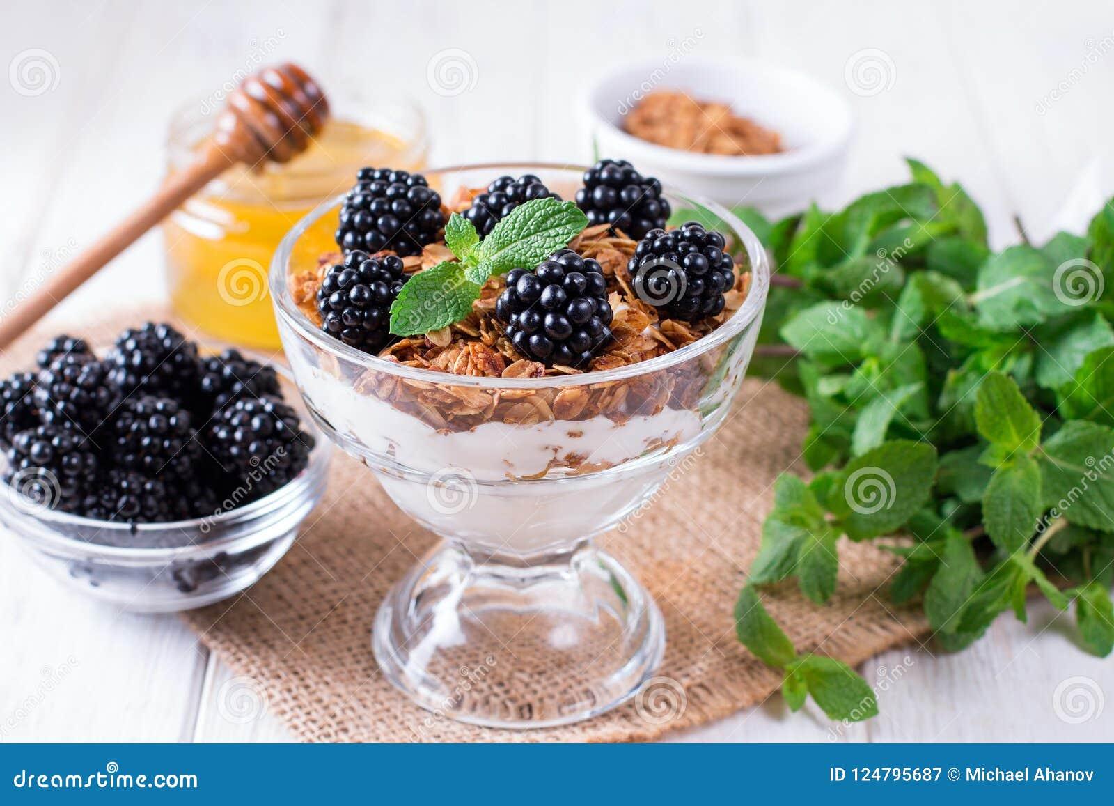 Zdrowy płatowaty deser z jogurtem, granola, czernica w szkle na drewnianym tle