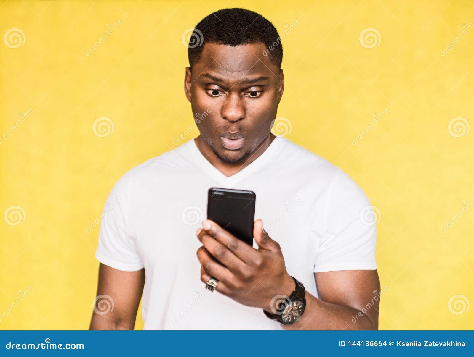 Zdumiony i zmartwiony przystojny amerykanin afrykańskiego pochodzenia mężczyzna trzyma smartphone, gapi się z zdziwionym wyrażeni