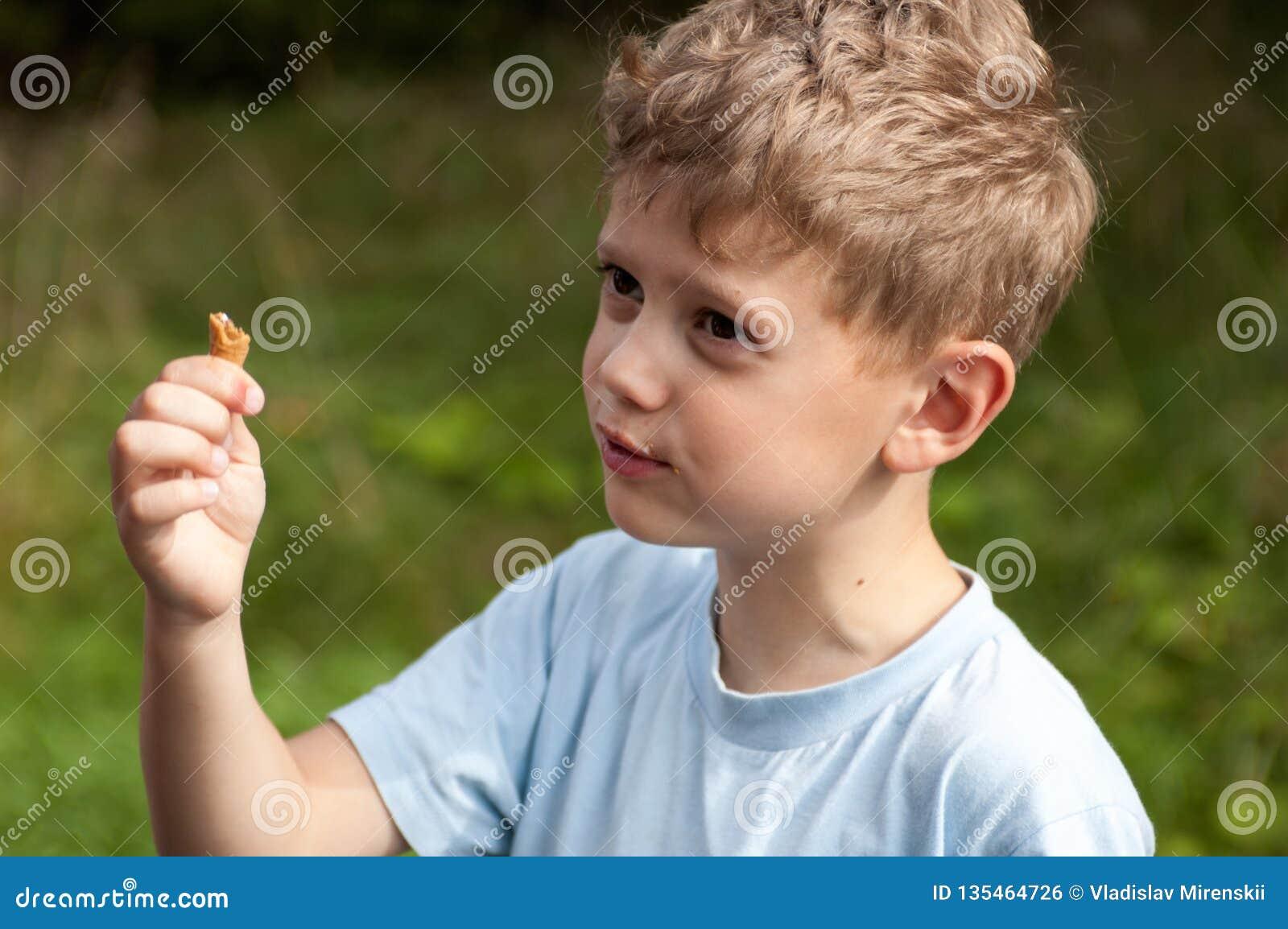 Zdziwiona chłopiec w resztkach lody konusuje w ręce