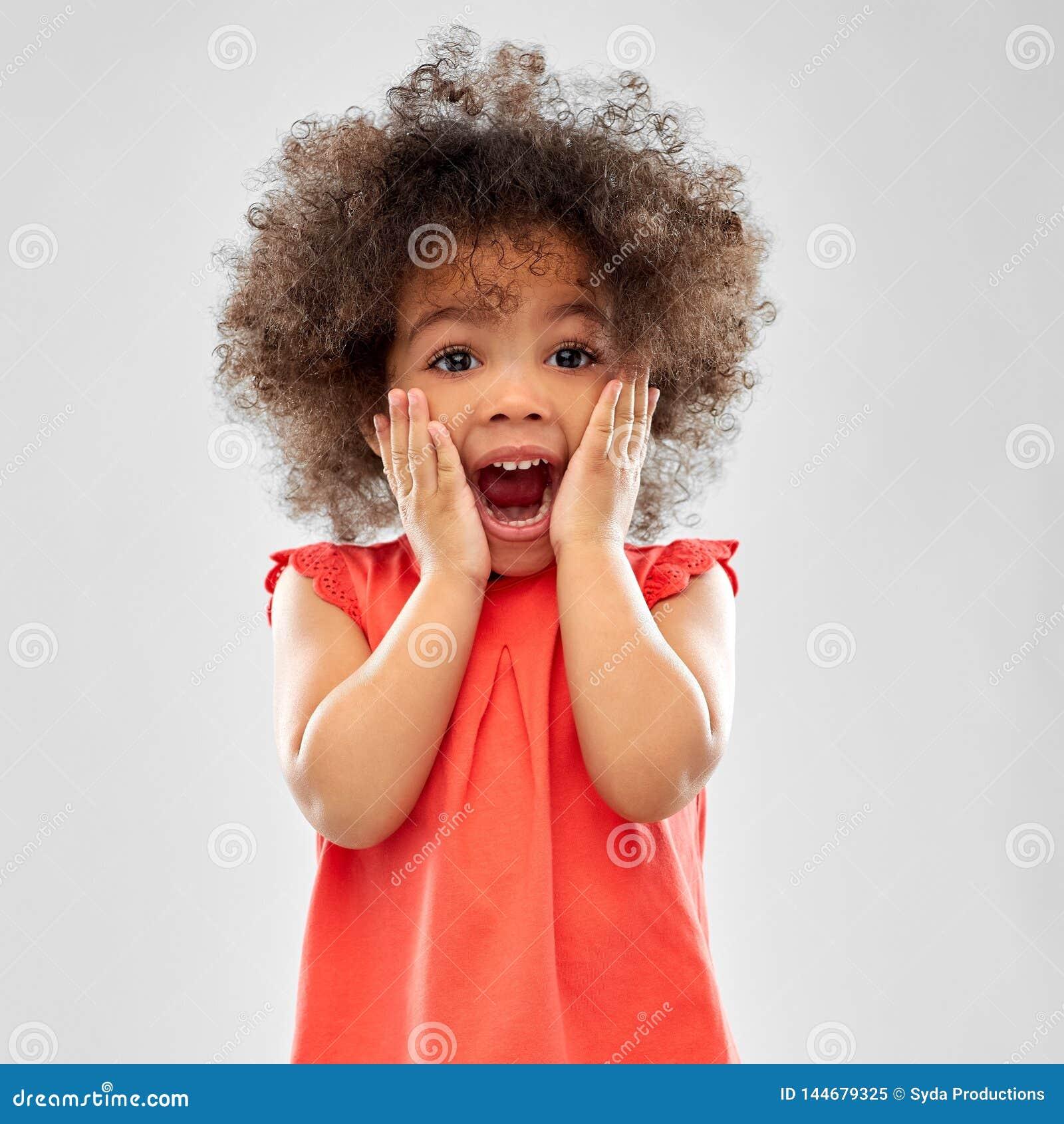 Zdziwiona lub strasząca mała amerykanin afrykańskiego pochodzenia dziewczyna