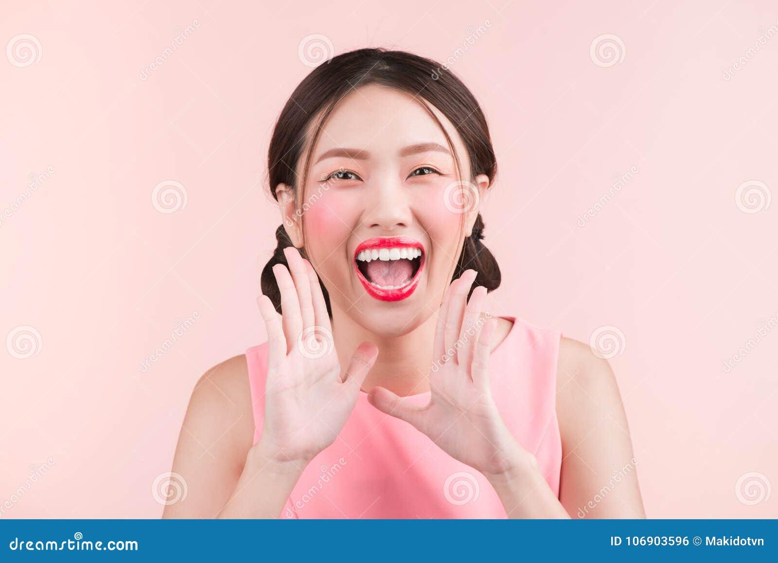 Zdziwiona młoda azjatykcia kobieta krzyczy nad różowym tłem