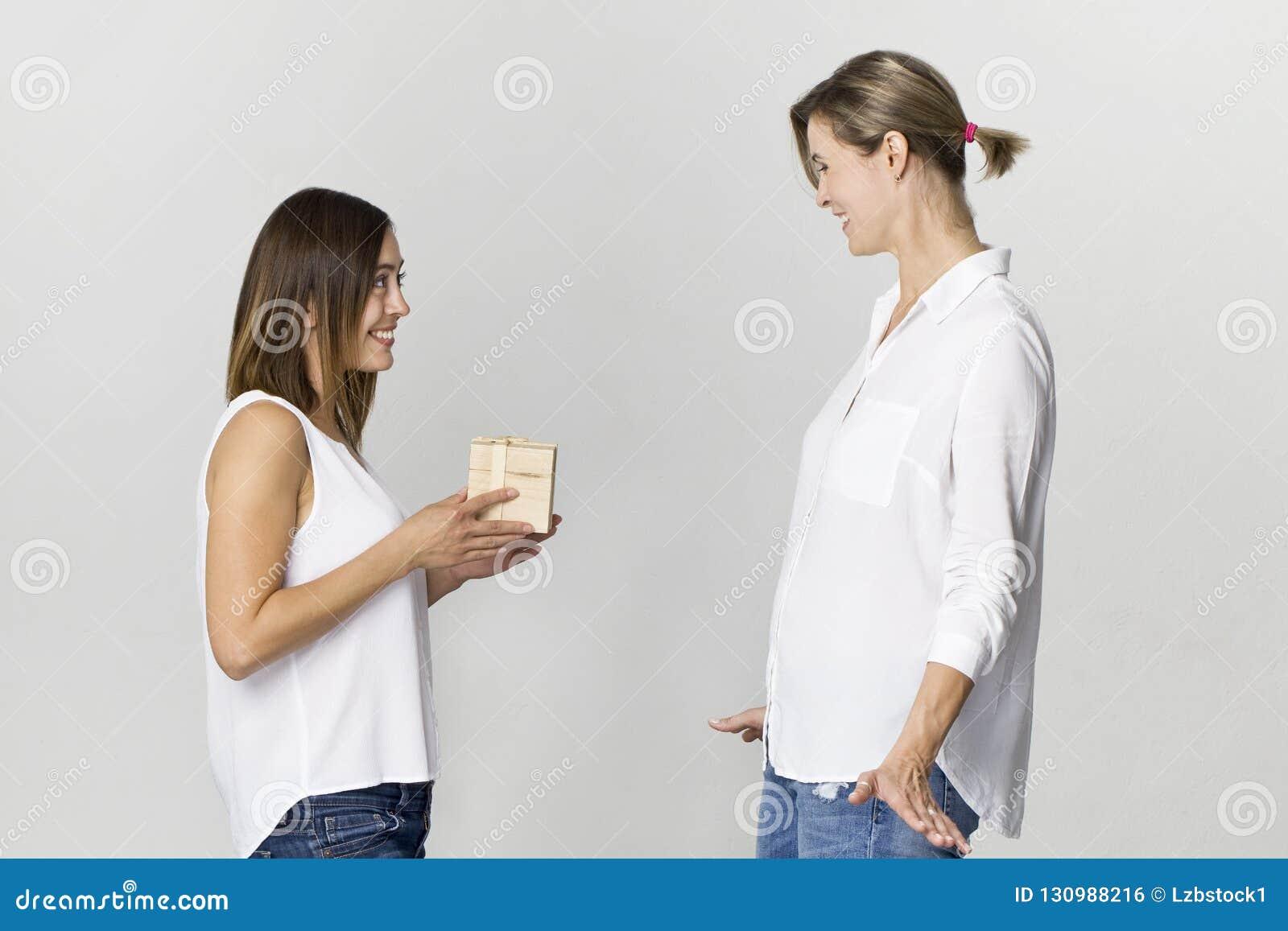 Zdziwiona młoda kobieta dostaje prezent od jej przyjaciela Szczęśliwi i uśmiechnięci żeńscy przyjaciele