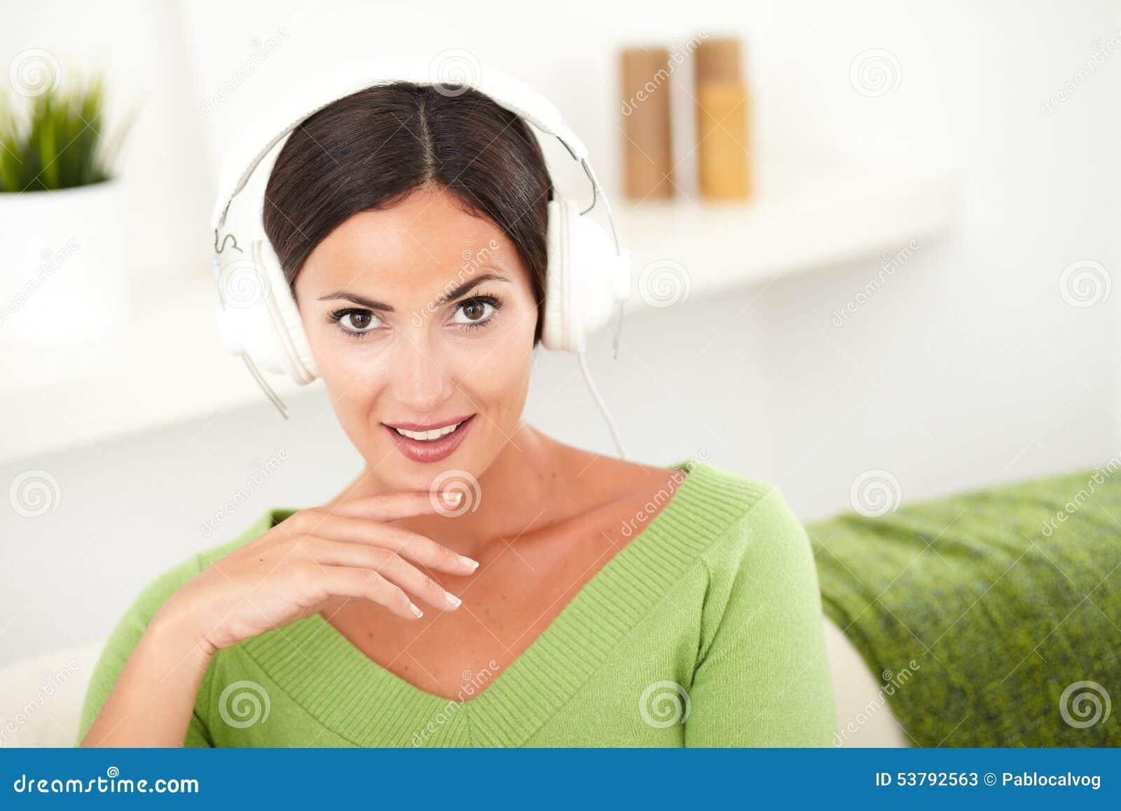Zdziwiona młoda kobieta słucha muzyka