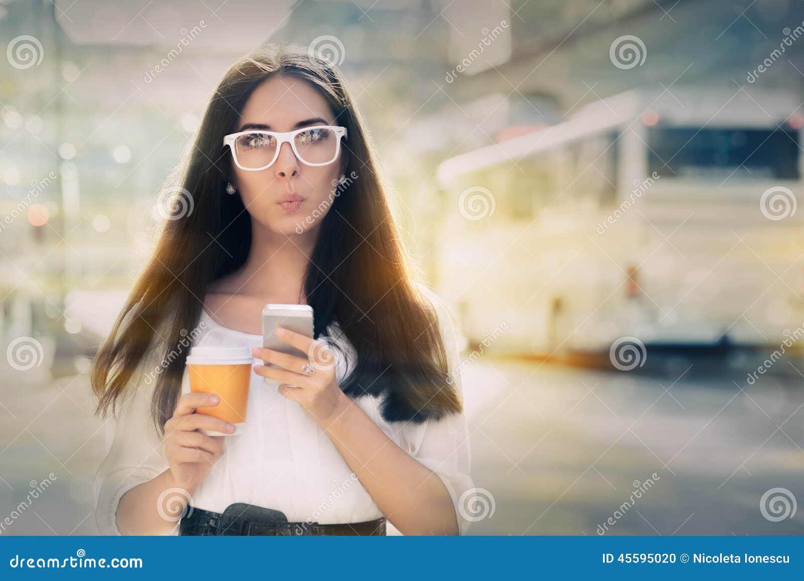 Zdziwiona młoda kobieta Trzyma Smartphone i filiżankę