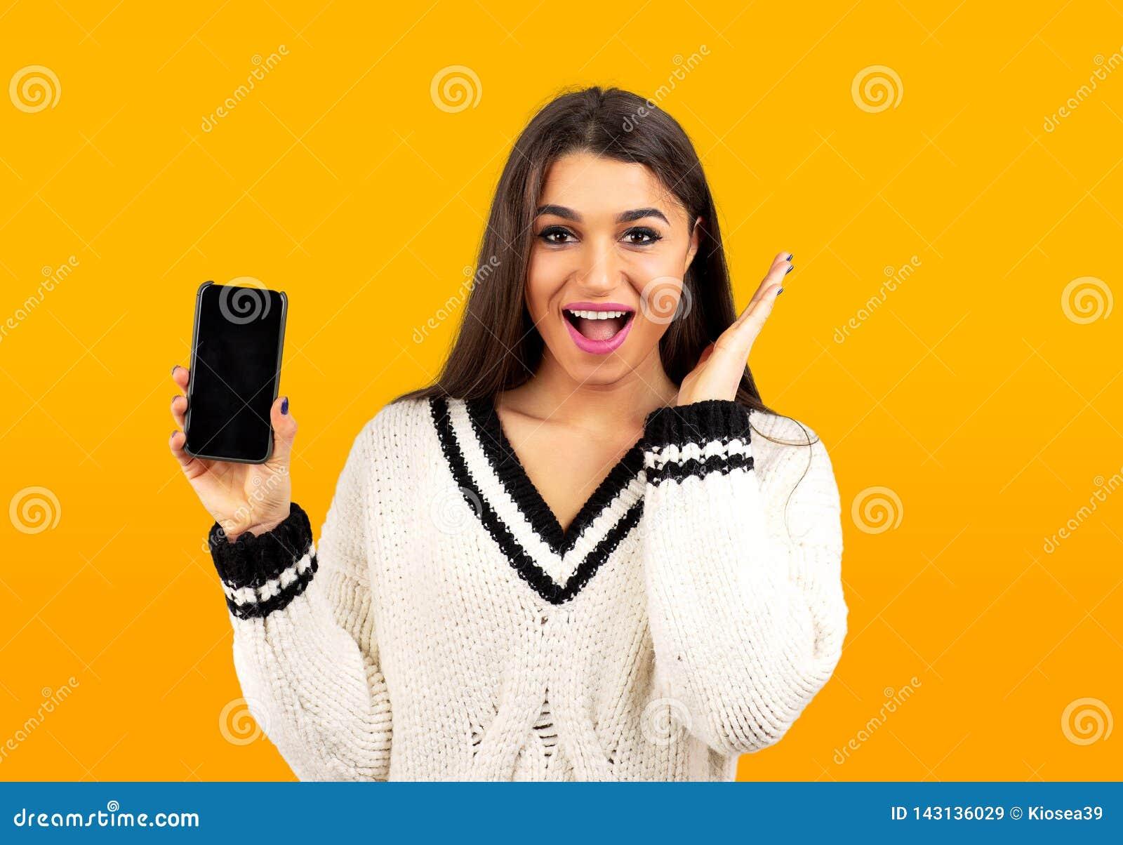 Zdziwiona szczęśliwa kobieta w białym pulowerze pokazuje nowego smartphone