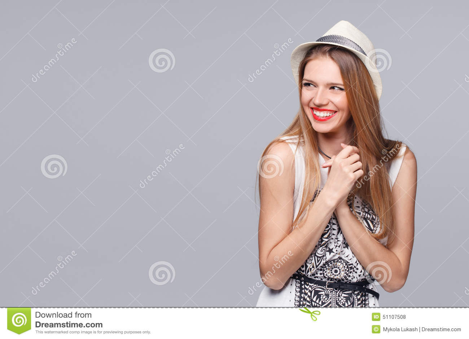 Zdziwiona szczęśliwa młoda kobieta patrzeje z ukosa w podnieceniu Odizolowywający nad szarość