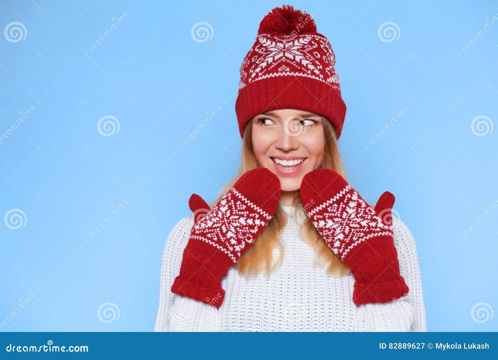 Zdziwiona szczęśliwa piękna kobieta patrzeje z ukosa w podnieceniu Bożenarodzeniowa dziewczyna jest ubranym dziać ciepłe mitynki