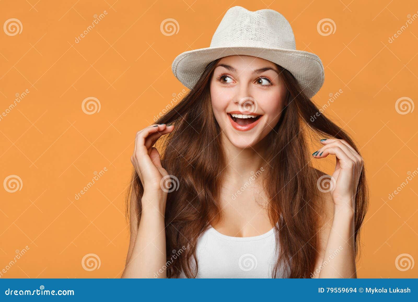 Zdziwiona szczęśliwa piękna kobieta patrzeje z ukosa w podnieceniu, odizolowywającym na pomarańczowym tle