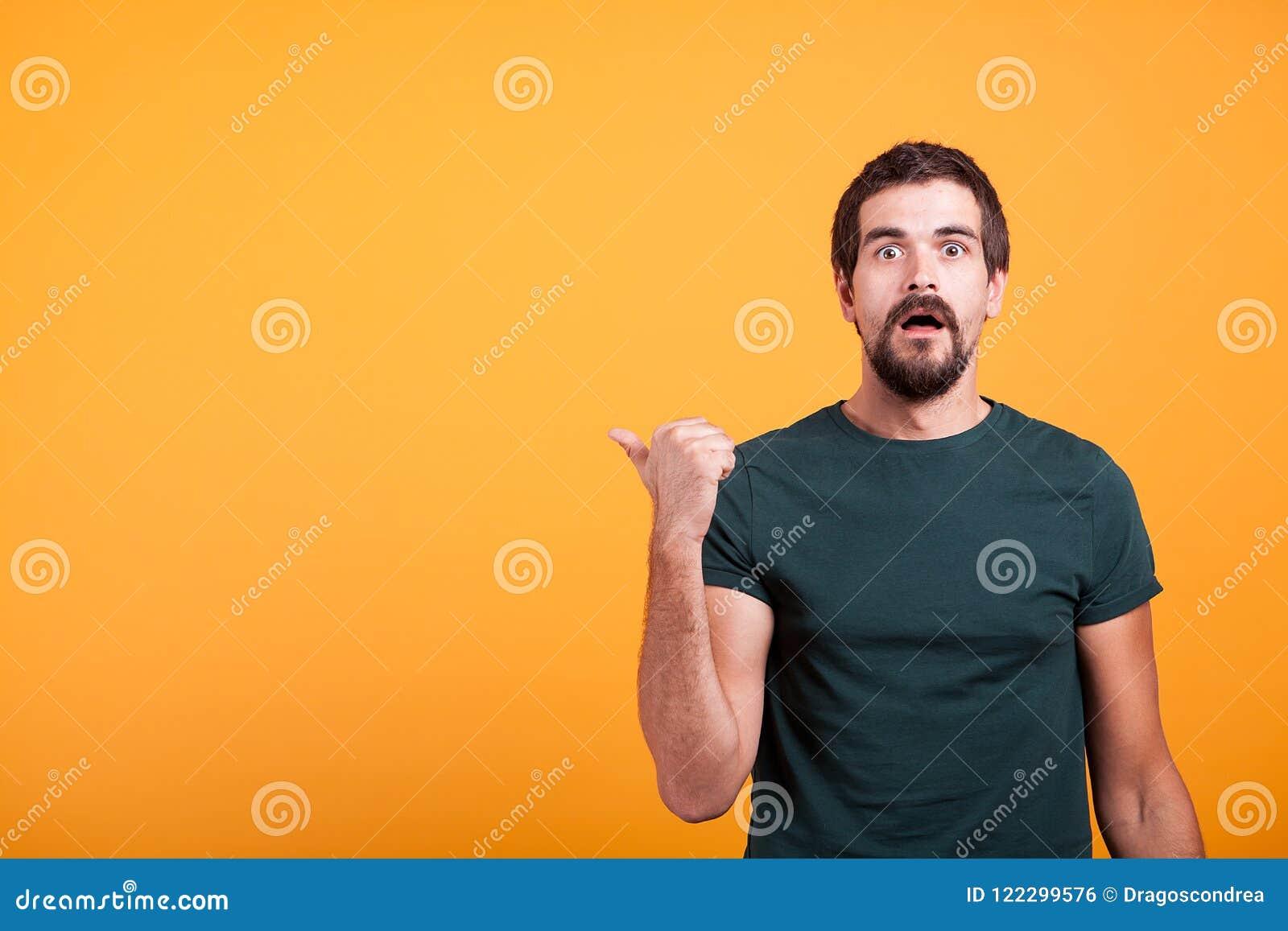 Zdziwiony emocjonalny dorosły mężczyzna wskazuje przy copyspace