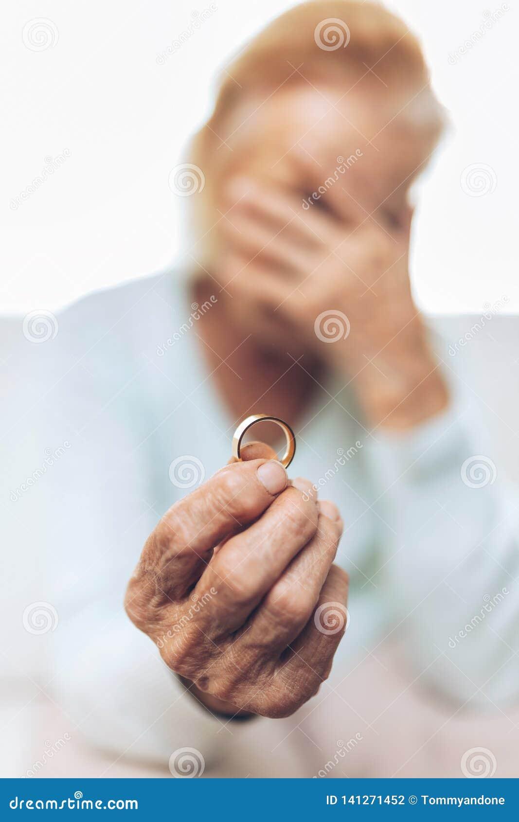 Ze złamanym sercem starsza kobieta trzyma obrączkę ślubną