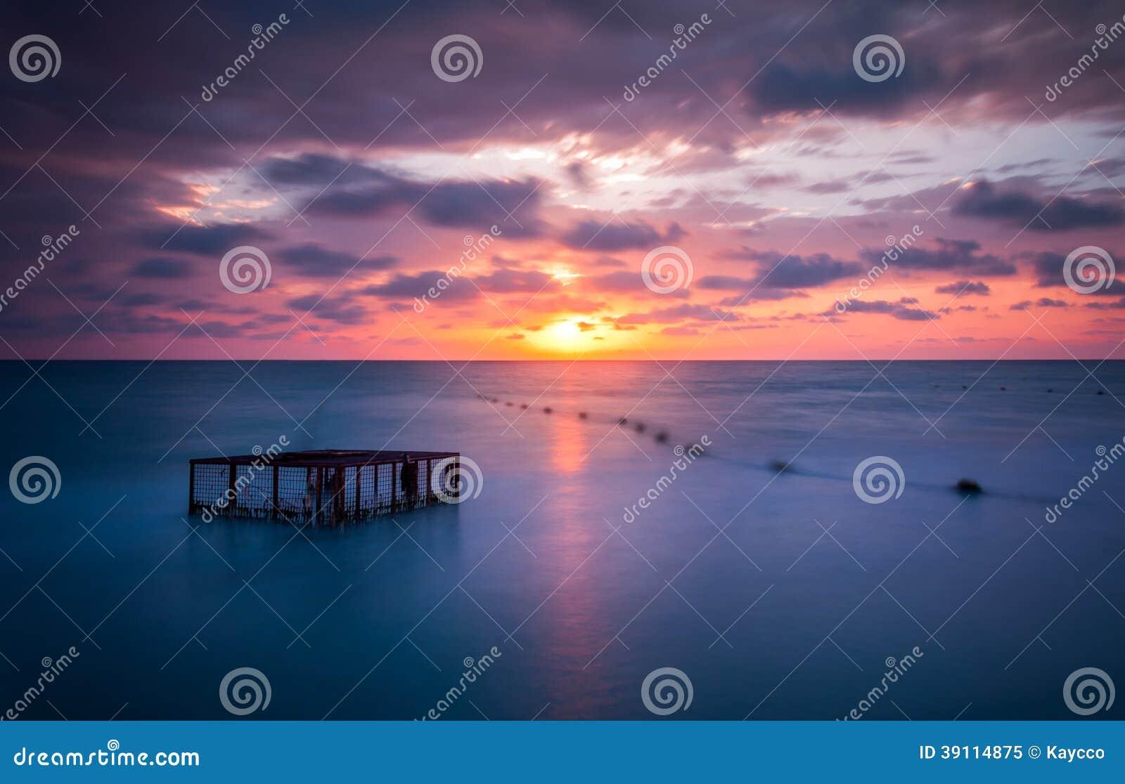 Zeegezicht en Lege Kooi bij Kleurrijke Zonsondergang