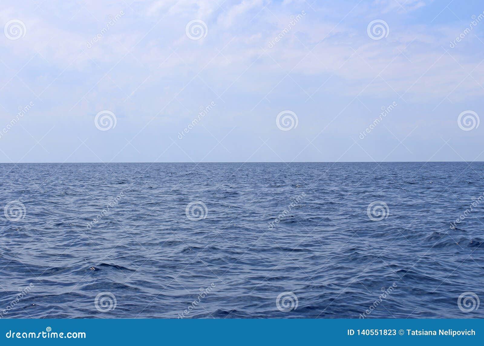 Zeegezicht met overzeese horizon en bijna duidelijke diepe blauwe hemel Achtergrond