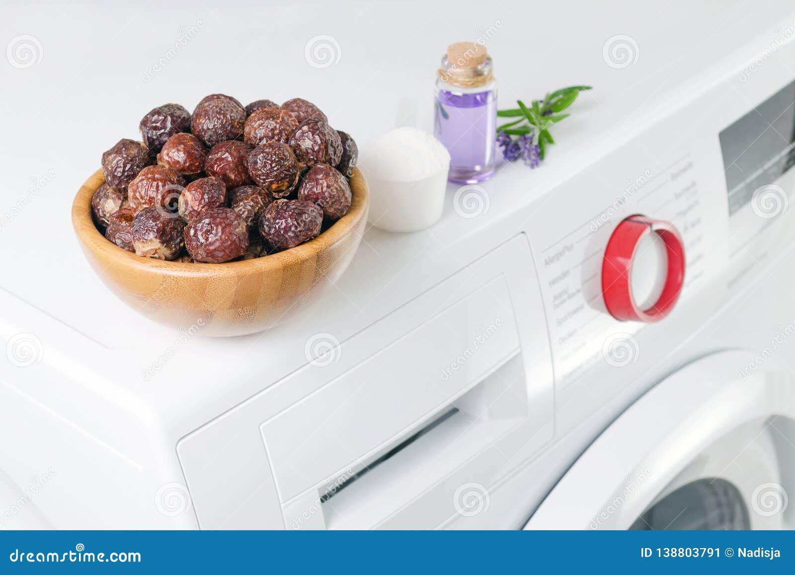 Zeepnoten in een kom op de wasmachine en lavendelolie, detergent poeder, selectieve nadruk