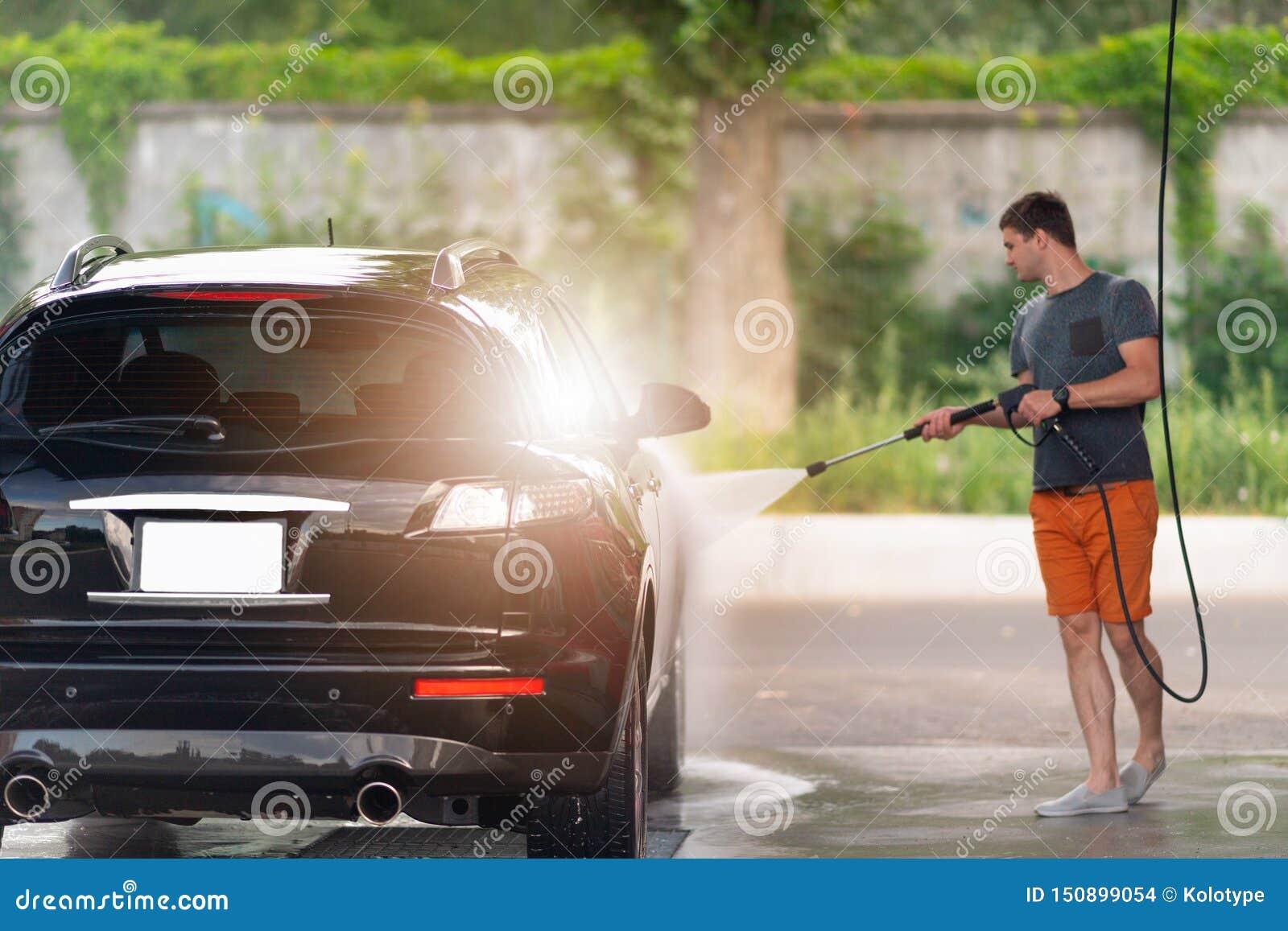 Zeepsop van de jonge mensen het hosing zeep van zijn auto