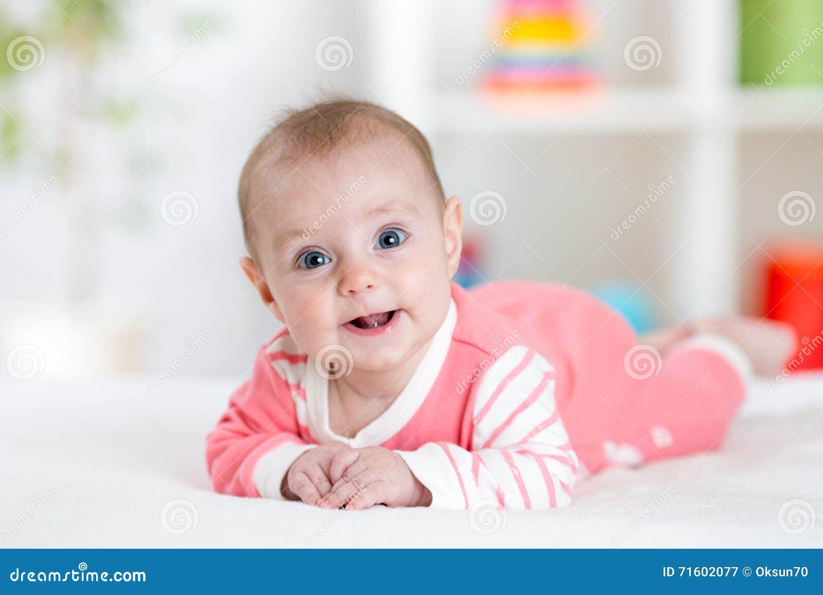 Zeer gelukkige lachende baby in roze kleren die op zijn buik liggen Zuigeling die recht de camera bekijken