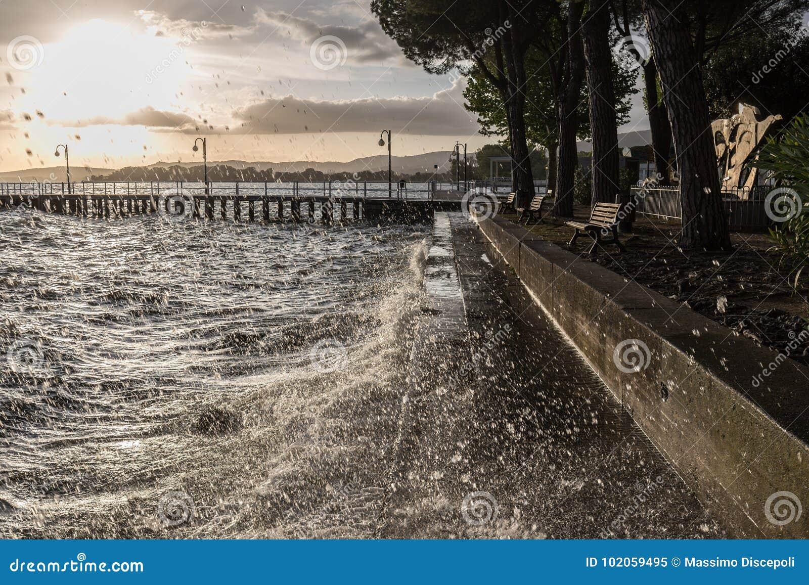 Zeer hoogwatergolven die op een meerkust bespatten, met dalingencomi