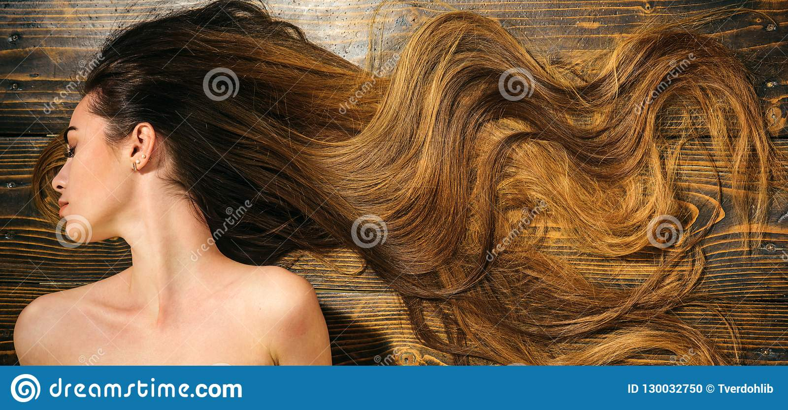 Zeer lang haar op houten achtergrond Mooi model met krullend kapsel Het concept van de haarsalon Zorg en haarproducten