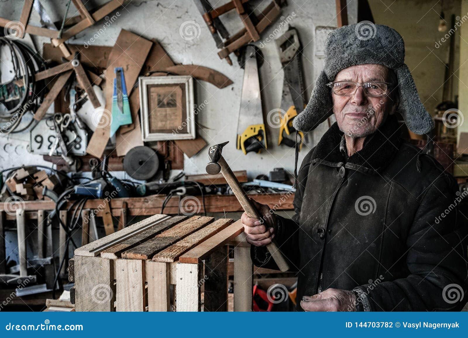 Zeer oude mensenmeester in grijze warme kleren en oogglazen met hamer in handen