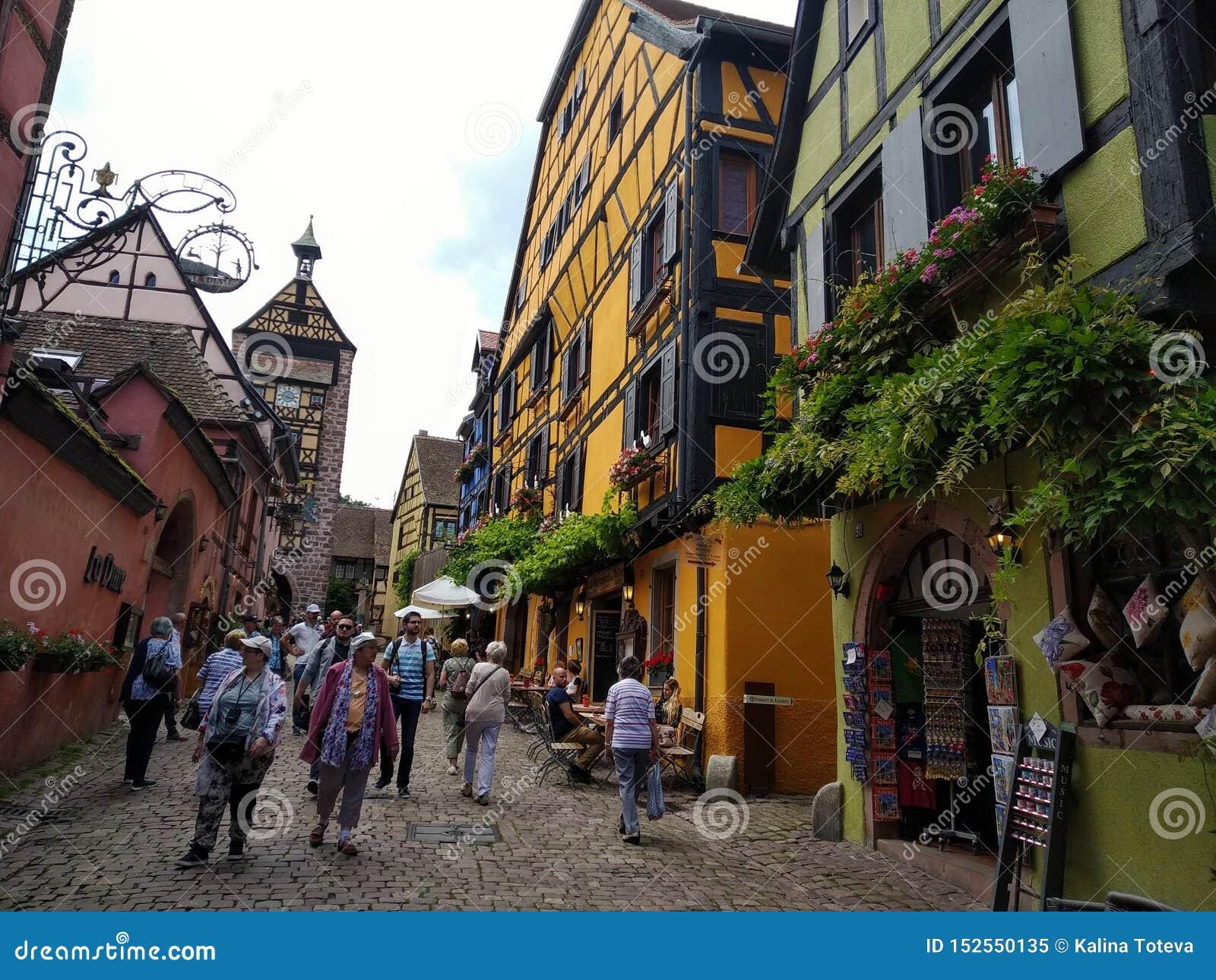 Zegarowy wierza, tradycyjni domy z kolorowymi fasadami i pochylanie dachy w Riquewihr, Francja