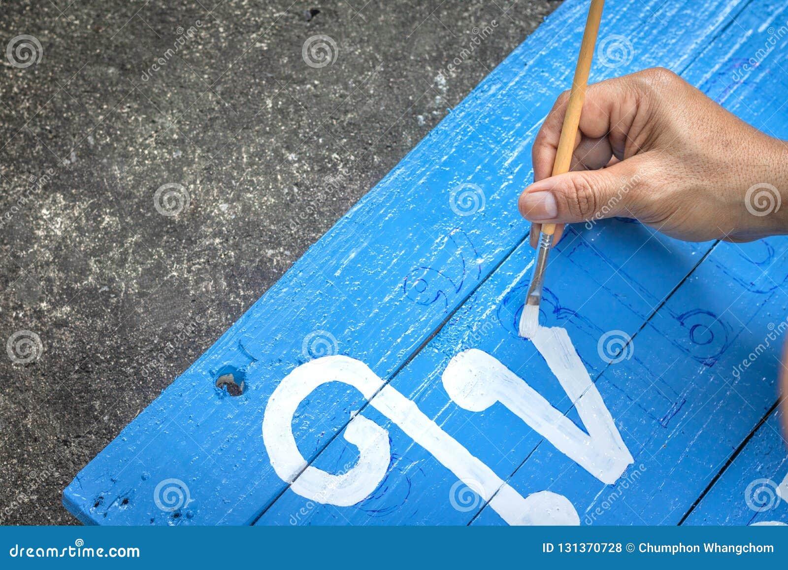 Zeichen schreibend, verschalen Sie mit einer Bürste von Aquarellen auf Zementbodenhintergrund Malerei auf hölzernem Brett in der