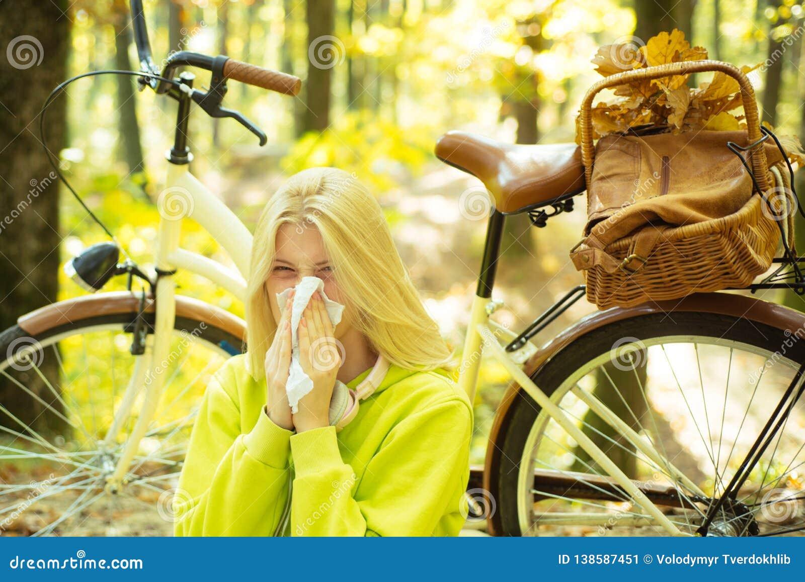 Zeigen der kranken Frau, die am Park niest Krankes Mädchen mit Kälte- und Grippestellung draußen