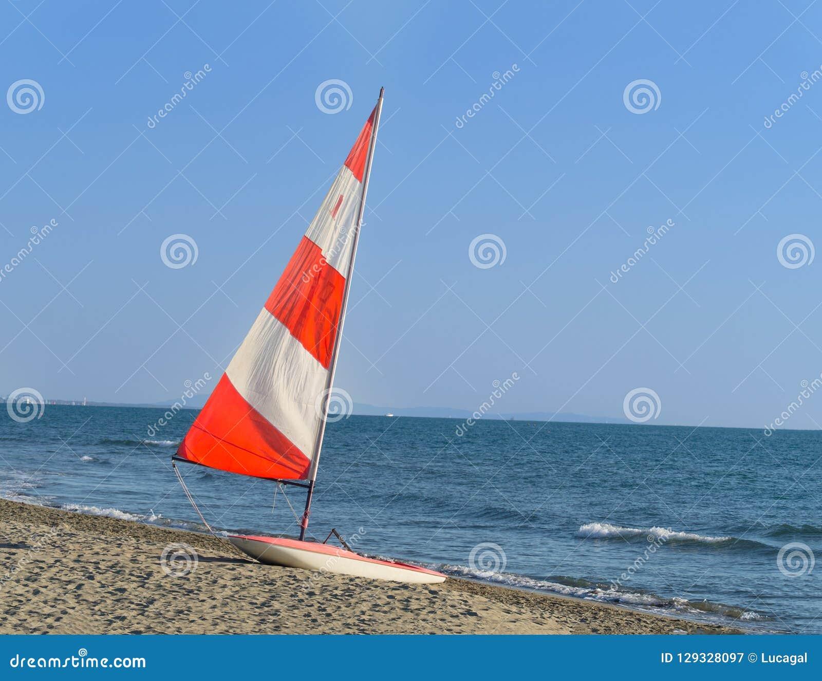 Zeilboot met rood en wit kleurrijk zeil op het strand