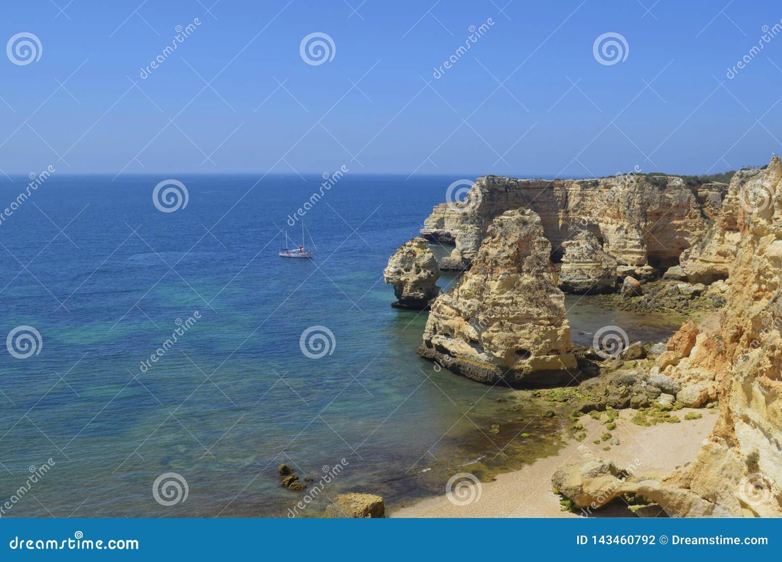 Zeilboot op verlaten strand en klippen