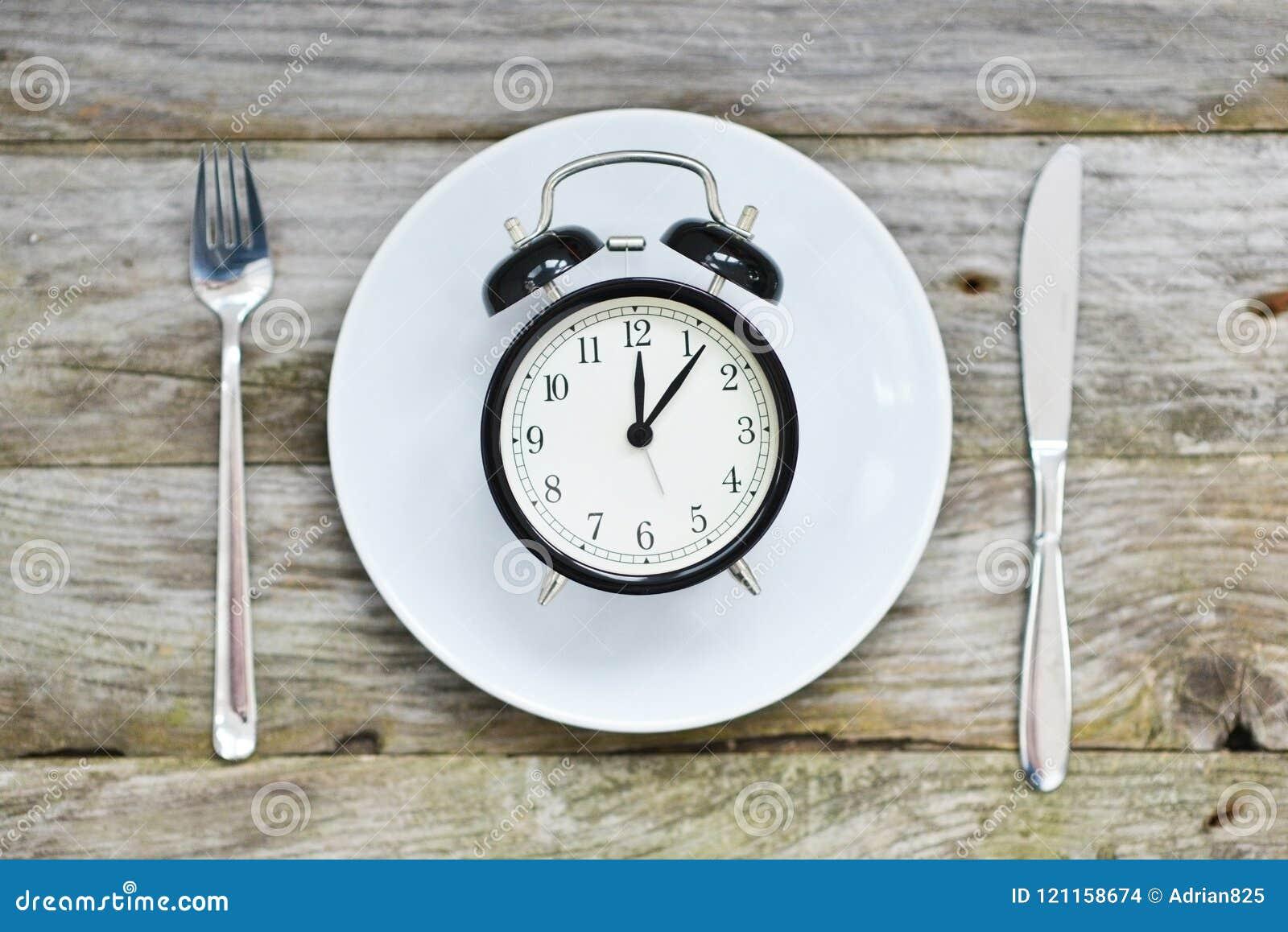 Zeit, mit Uhrplattengabel und -messer auf einer Tabelle zu essen