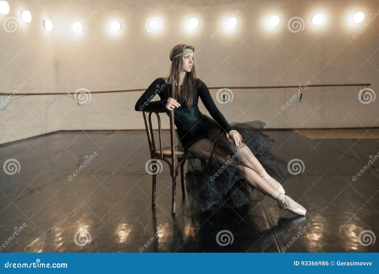 Zeitgenössischer Balletttänzer auf einem Holzstuhl auf einer Wiederholung