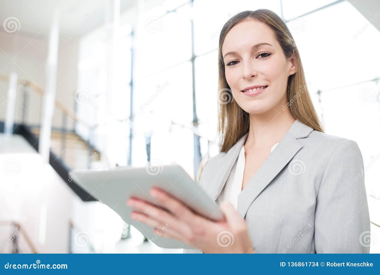 Zekere de Tabletcomputer van Onderneemstersmiling while holding