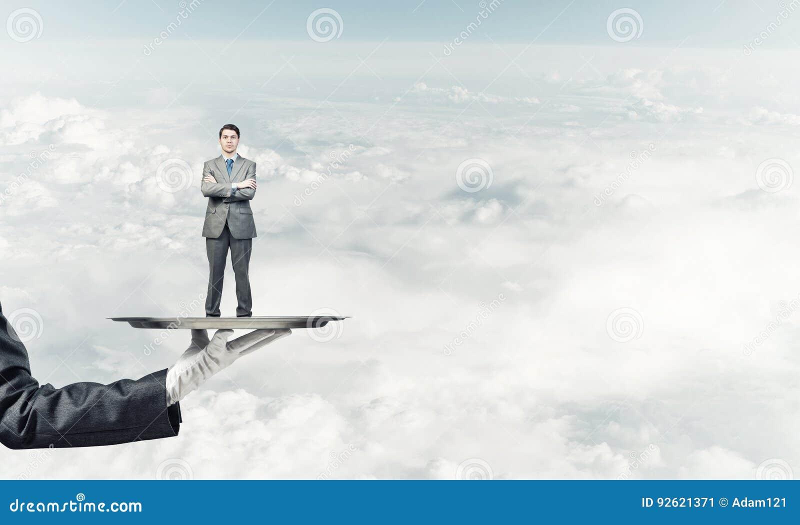 Zekere die zakenman op metaaldienblad tegen blauwe hemelachtergrond wordt voorgesteld
