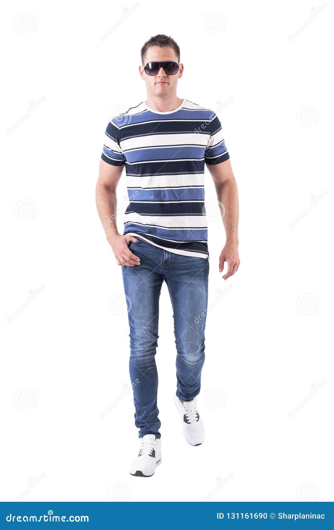 Zekere ernstige machomens die met zonnebril en jeans naar camera met intense blik lopen