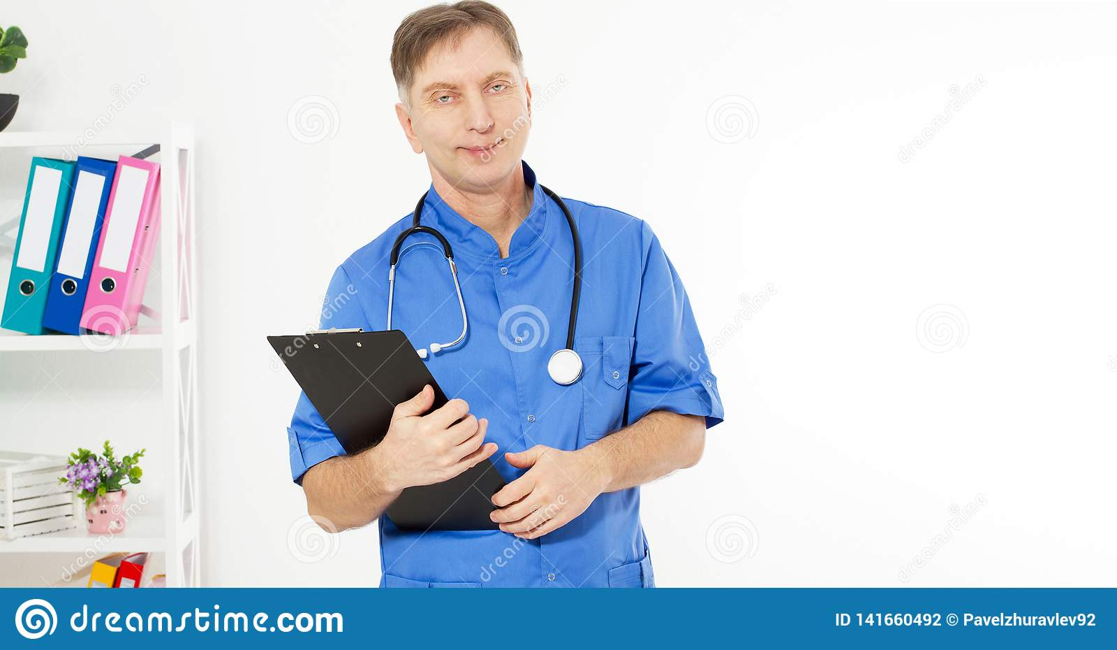 Zekere glimlachende arts die en camera met zwarte omslag, medische bureaukliniek op de achtergrond stellen bekijken, exemplaarrui
