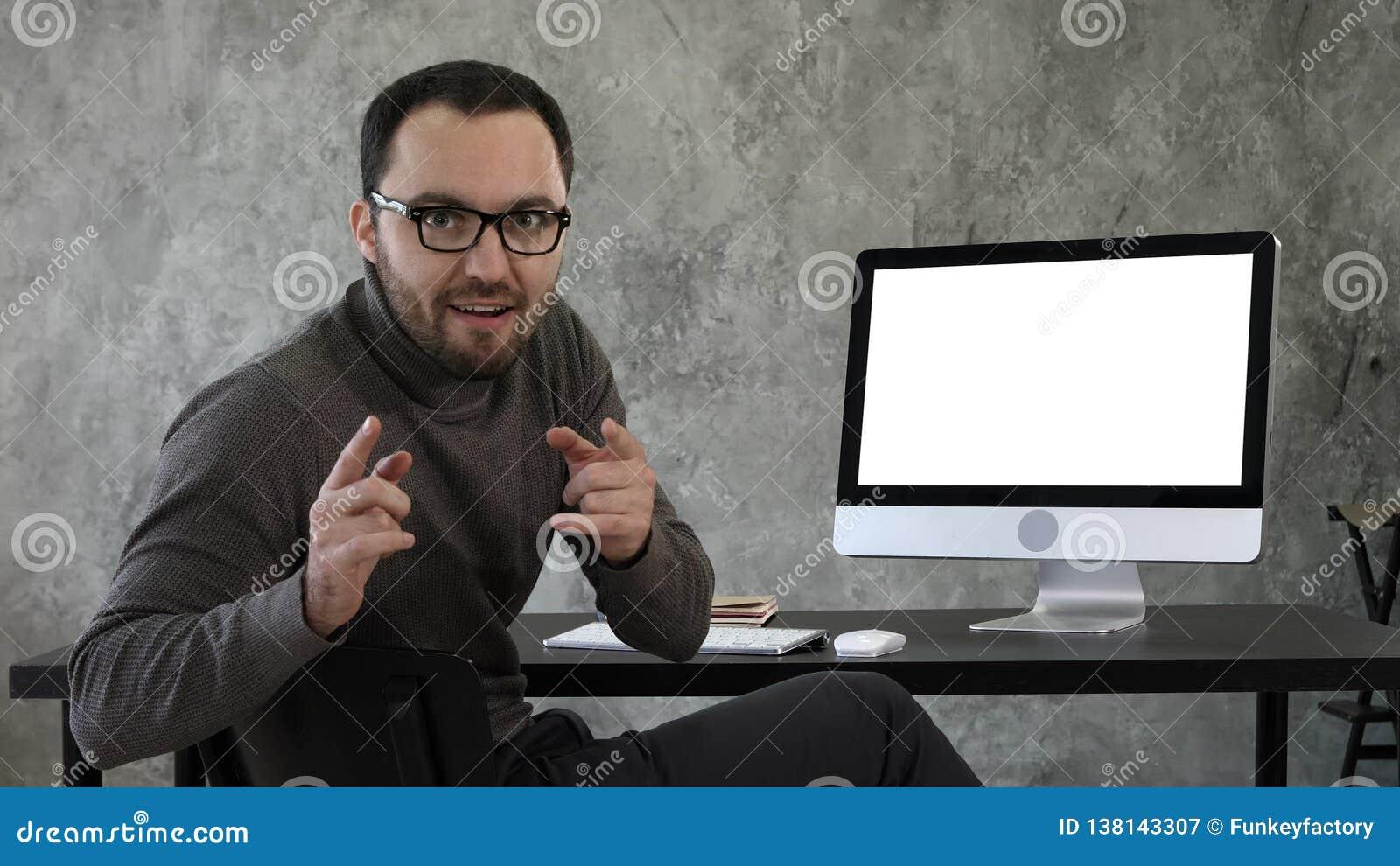 Zekere jonge mens die camera bekijken die op een zeer zekere manier dichtbij het computerscherm spreken Witte vertoning