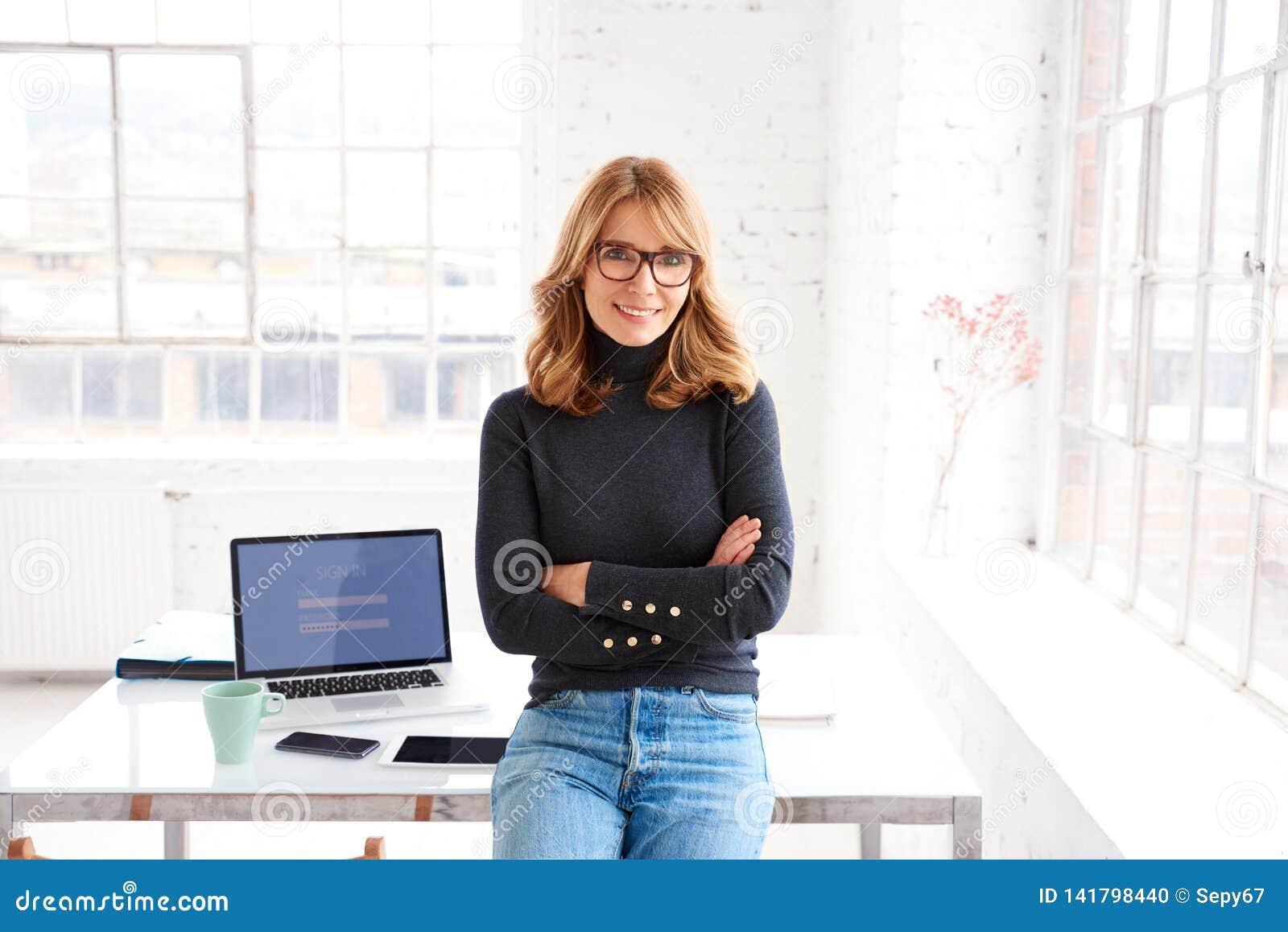Zekere onderneemster die aan u glimlachen en camera bekijken terwijl status in het bureau
